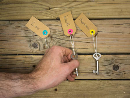 path to wealth: life choices concept: old keys hanging on rusty nails against wooden background with labels love, wealth and happiness and a mans hand choosing the key to wealth