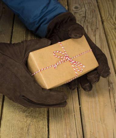 deliveryman: dettaglio di mans mani in cappotto e guanti in possesso di una stringa e pacchi di carta marrone su un tavolo di legno rustico