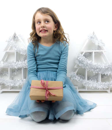 7 year old girl: little smiling curly haired girl sitting holding a traditional christmas present with christmas decorations Stock Photo