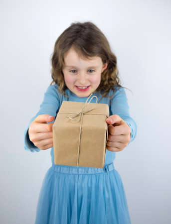 7 year old girl: small smiling girl receiving a present wrapped in brown paper and string, focus on gift