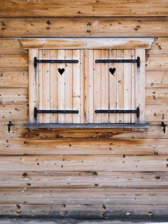 forground: detail of wooden shutters on a rustic wooden cabin window with heart  shapes and falling snowflakes in forground Stock Photo
