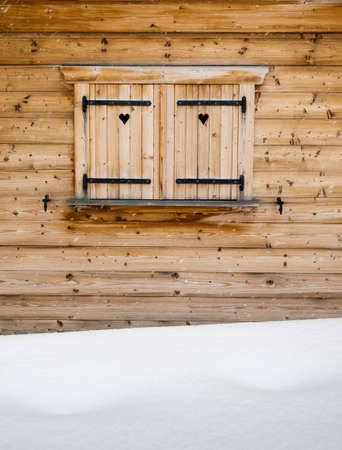 forground: detail of wooden shutters on a rustic wooden cabin window with heart  shapes and falling snowflakes and snowdrift in forground Stock Photo
