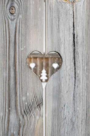 heart motif in grey aged wooden shutterboard fence with  with tree and heart motifs  out of focus in fence behind and falling snowfalkes out of focus in forground