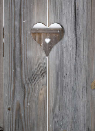 heart motif in grey aged wooden shutterboard fence with  with heart motif  out of focus in fence behind and falling snowfalkes