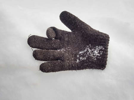 childs: lost childs woolen glove lying on the snow