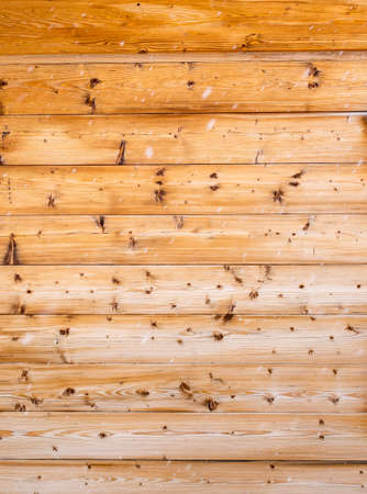 knotted pine wooden cabin wall with falling snow with movement blur in foreground Stock Photo