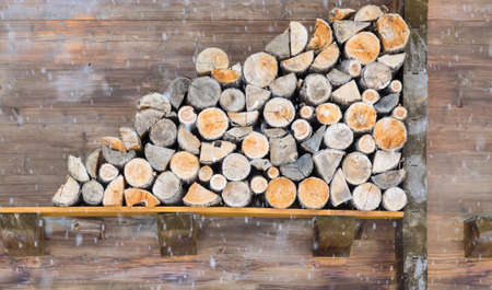 stack of sawn logs against and olf cabin wall with falling snow in teh foreground