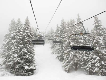 wintersport: empty ski lift in mist between snow covered trees Stock Photo