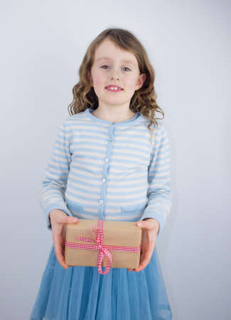 little smiling girl giving a present wrapped in brown paper with a check ribbon