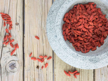 closeup of dried goji berries in a rustic stone bowl  on an aged wooden table top Stock Photo
