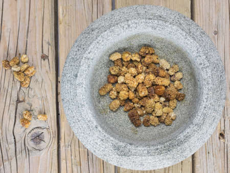 dried mulberries in a stone bowl against a rustic old wooden table top