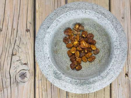 dried inca berries in a rustic stone bowl with an old wooden table top behind Stock Photo