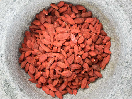 wolfberry: closeup of dried goji berries in a rustic stone bowl Stock Photo