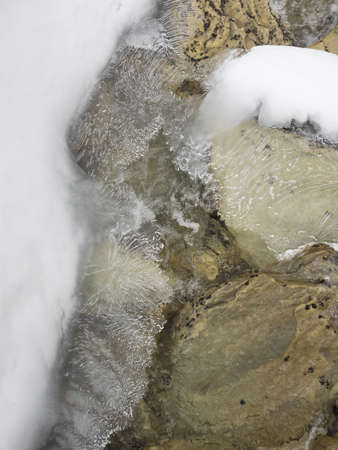 flowing stream with layers of ice and snow
