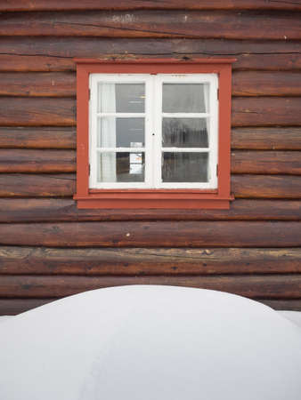 detail of  wooden cabin with snowdrift in foreground