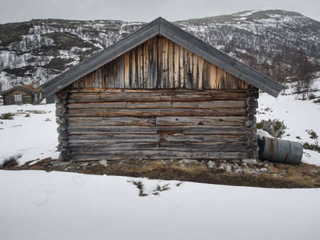 outhouse: old weathered wooden cabin in a snowy winter mountain landscape