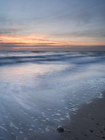 long exposure of beach and surf at last light with motion blur