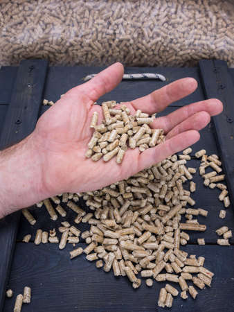 domestication: mans hand showing wood pellets with loose wood pellets, trap door and wood pellets stored in sacks behind
