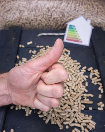 wood pellet: mans hand giving a thumbs up sign with wood pellet store and energy lable behind Stock Photo