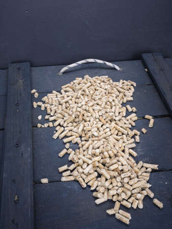 domestication: wood  pelletson a trap door  in a wood store Stock Photo