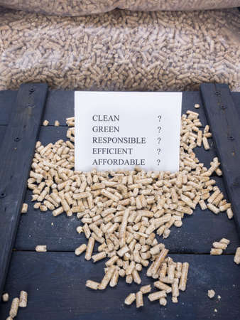 wood tick: wood pellets in a wood pellet store with a check list carrying the words clean, green, responsible, efficient and affordable with question marks against each-concept questioning environmental benefit of wood pellet fuels
