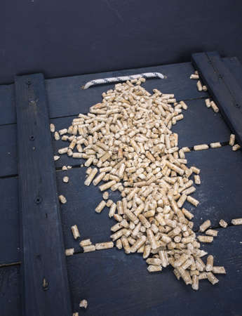 fuel and power generation: wood  pelletson a trap door  in a wood store Stock Photo