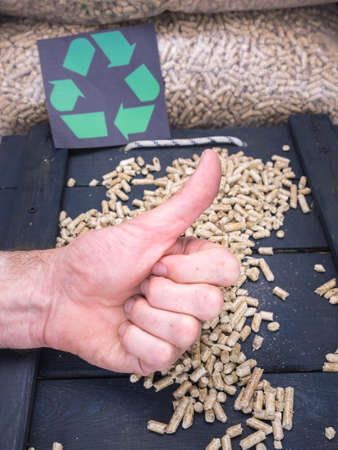wood pellet: mans hand gives thumbs up with wood pellet store and recycling label behind