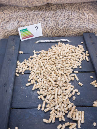 domestication: wood pellets on a trap door in wood pellet store with energy lable and question mark-conceptual image questioning ecological value of wood pellets Stock Photo