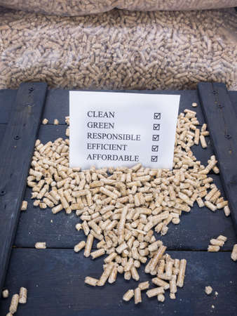 wood pellet: wood pellets in a wood pellet store with a check list carrying the words clean, green, responsible, efficient and affordable checked off