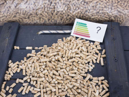 wood pellet: wood pellets on a trap door in wood pellet store with energy lable and question mark-conceptual image questioning ecological value of wood pellets Stock Photo