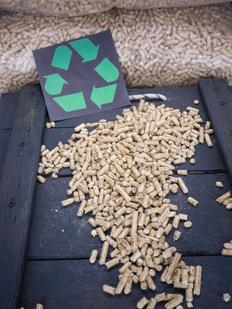wood pellet: wood pellets in a wood pellet store with recycling symol behind Stock Photo