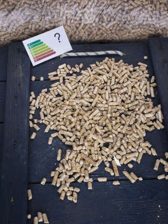 validez: pellets de madera en una puerta de la trampa en la tienda de pellets de madera con lable de la energía y la imagen de marca conceptual pregunta que cuestionan el valor ecológico de los pellets de madera Foto de archivo