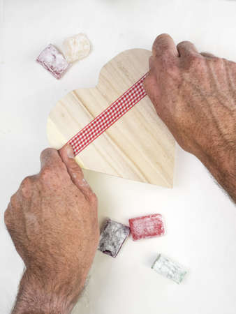 mans hands wrapping a rustic wooden heart shaped presentation box with a gingham ribbon. colourful turkish delight and white surface behind Stock Photo