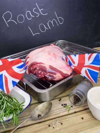 roast lamb: raw  lamb joint on roasting tin with ingredients for roast lamb and blackboard behind with text roast lamb and british flags