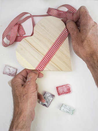 mans hands tying checked ribbon  on a rustic wooden heart shaped presentation box with colourful turkish delight and white surface behind