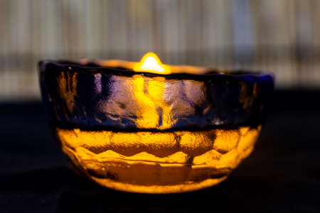 A candle in a small colored glass dish full of colored water.