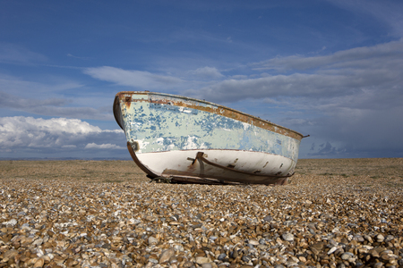 shingle beach: A solitary fishing boat on a shingle beach.