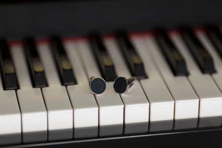 cuff link: Cuffs on piano