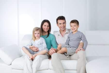 parents with child sit on modern sofa Stock Photo
