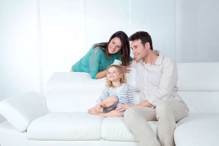 mom dad and daughter sitting on the sofa watching