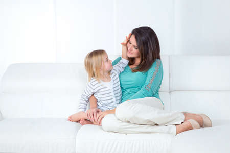 caresses: loving little girl caresses her young mother