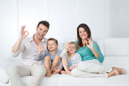 mom, dad and children saying okay with hands