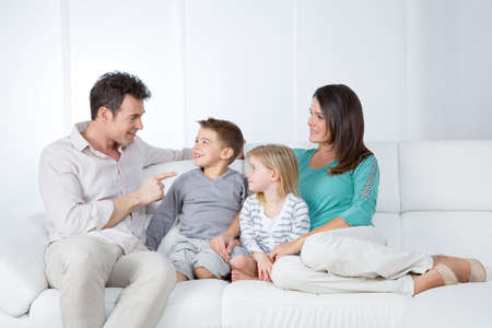 family sofa: young father joking with his little child