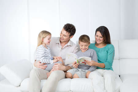 young family laughs happily on white sofa photo