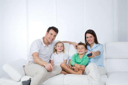 Mère change émission à la télévision avec télécommande Banque d'images - 33918425