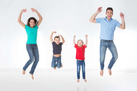 red jeans: mother, father and their children jumping together