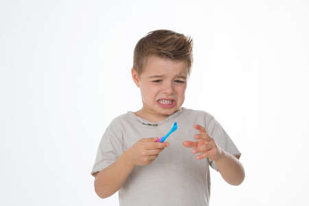 blue plaque: little kid unwilling to brush his teeth Stock Photo