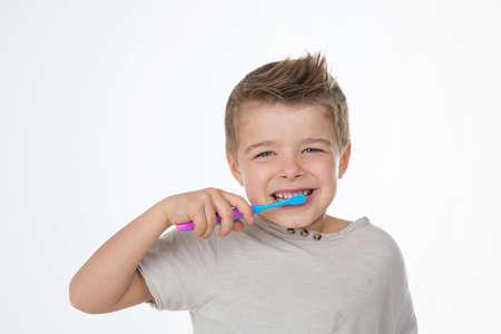 funny kid enjoys his toothbrush Imagens