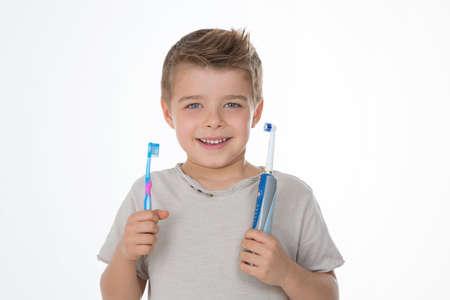Kid montre ses brosses à dents manuelles et électriques Banque d'images - 33983009
