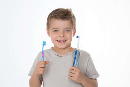 kid shows his manual and electric toothbrushes Imagens